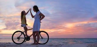 Mutter und Tochter auf einem Fahrrad Stockbilder