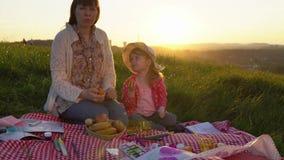Mutter und Tochter auf einem Picknick auf einem Hügel im Sommer bei Sonnenuntergang stock video