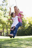 Mutter und Tochter auf Gartenschwingen Stockfoto
