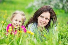 Mutter und Tochter auf grüner Sommerwiese stockfotografie