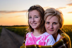Mutter und Tochter auf Land-Straße bei Sonnenuntergang stockbilder