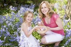 Mutter und Tochter auf Ostern, das nach Eiern sucht Stockbild