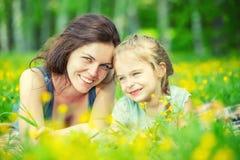 Mutter und Tochter auf sonniger Wiese lizenzfreie stockfotografie
