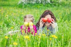 Mutter und Tochter auf sonniger Wiese mit Äpfeln in den Händen stockbild