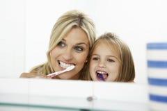 Mutter-und Tochter-bürstende Zähne zusammen Stockfotos