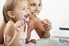 Mutter-und Tochter-bürstende Zähne zusammen Stockfoto