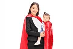 Mutter und Tochter bei der Superheldkostümaufstellung Stockfotos