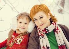 Mutter und Tochter, beide rotes Haar gehend in Kostüme von Sankt-` s Elfen der Blumen traditionellen Helfern im Winterwald stockfotos