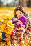 Mutter und Tochter beim Spielen im Herbstpark stockbild