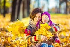 Mutter und Tochter beim Spielen im Herbstpark lizenzfreie stockbilder