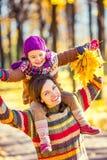 Mutter und Tochter beim Spielen im Herbstpark stockbilder
