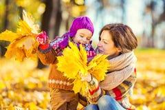 Mutter und Tochter beim Spielen im Herbstpark stockfoto