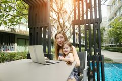 Mutter und Tochter benutzen Laptop für das on-line-Einkaufen auf Hintergrund des Swimmingpools am sonnigen Tag lizenzfreie stockfotografie