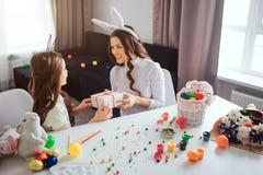 Mutter und Tochter bereiten sich für Ostern vor, das im Raum festlich ist Griffgeschenk der jungen Frau in den Händen für Mädchen stockfotografie