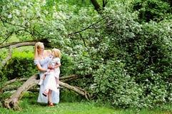 Mutter und Tochter in blühendem Garten Stockfotos