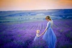 Mutter und Tochter in den schönen Kleidern auf dem Lavendelgebiet lizenzfreies stockfoto