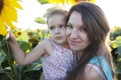 Mutter und Tochter in den Sonnenblumen Stockfoto