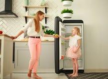 Mutter und Tochter in der Küche setzten Früchte und Äpfel in Kühlschrank, gesunden Lebensstil der Hauptfamilie ein stockfotos