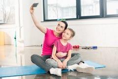 Mutter und Tochter in der Sportkleidung, die auf Matte sitzt und selfie nimmt Lizenzfreies Stockbild