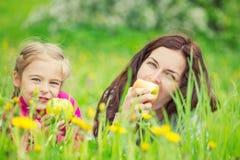 Mutter und Tochter, die Äpfel auf grüner Sommerwiese essen lizenzfreies stockfoto