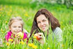 Mutter und Tochter, die Äpfel auf grüner Sommerwiese essen lizenzfreies stockbild