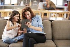 Mutter und Tochter, die auf Aufenthaltsraum Sofa Using Digital Devices sitzen stockbild