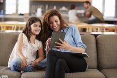 Mutter und Tochter, die auf Aufenthaltsraum Sofa Using Digital Devices sitzen stockfotos