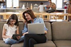 Mutter und Tochter, die auf Aufenthaltsraum Sofa Using Digital Devices sitzen stockbilder
