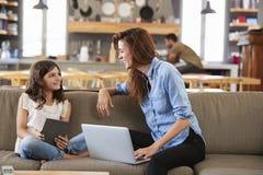 Mutter und Tochter, die auf Aufenthaltsraum Sofa Using Digital Devices sitzen lizenzfreie stockfotografie