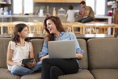 Mutter und Tochter, die auf Aufenthaltsraum Sofa Using Digital Devices sitzen lizenzfreie stockfotos