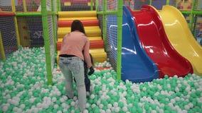 Mutter und Tochter, die auf Bälle auf Spielplatz in der Mitte der Kinder gehen stock footage