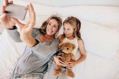 Mutter und Tochter, die auf Bett liegen und selfie nehmen Lizenzfreies Stockfoto