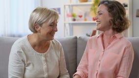 Mutter und Tochter, die auf Couch, die guten Nachrichten teilend lacht und vertrauen Gespräch stock video footage
