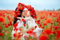 Mutter und Tochter, die auf dem Blumengebiet spielen lizenzfreies stockbild