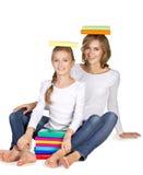 Mutter und Tochter, die auf dem Boden mit Büchern auf gehört sitzt Lizenzfreies Stockbild