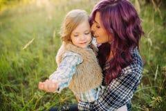 Mutter und Tochter, die auf dem Feld im Sonnenuntergang sitzen Lizenzfreies Stockfoto