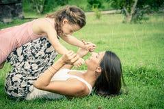 Mutter und Tochter, die auf dem Gras zur Tageszeit spielen Stockfotos