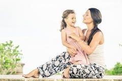Mutter und Tochter, die auf dem Gras zur Tageszeit spielen Lizenzfreies Stockfoto