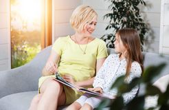 Mutter und Tochter, die auf dem Sofa sitzen stockbilder