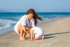 Mutter und Tochter, die auf dem Strand spielen Stockbilder