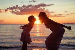 Mutter und Tochter, die auf dem Strand spielen Lizenzfreies Stockbild