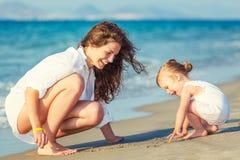 Mutter und Tochter, die auf dem Strand spielen lizenzfreies stockfoto