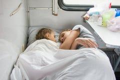 Mutter und Tochter, die auf dem unteren Regal in einem Zug schlafen Stockbilder