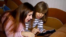 Mutter und Tochter, die auf der Couch betrachtet die Tablette, sprechend liegt stock video