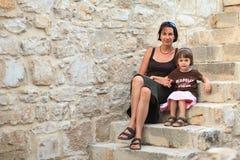 Mutter und Tochter, die auf der Steintreppe sitzen Lizenzfreie Stockfotos