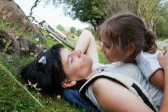 Mutter und Tochter, die auf einem Gras sich entspannen Stockbilder
