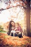 Mutter und Tochter, die auf gefallenen Blättern sitzen lizenzfreies stockbild
