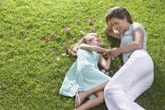 Mutter und Tochter, die auf Gras liegen Stockbilder