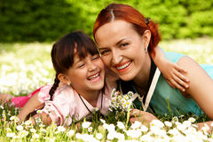Mutter und Tochter, die auf Gras liegen Stockbild