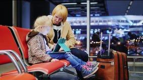 Mutter und Tochter, die auf Ihren Flug, kleines Mädchen spielt auf einer Tablette wartet stock footage